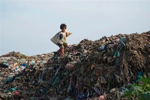 A child sorts through scraps in a rubbish dump. Photo / Supplied