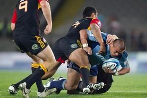 Blues Kevin Mealamu is tackled by Tanerau Latimer . Photo / Richard Robinson