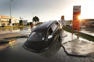 A car sinks in water on Ferry Road after the two magnitude 6.0 and 5.5 earthquakes struck yesterday. Photo / Getty Images