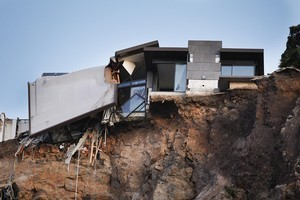 The remains of a damaged house at Shag Rock near Sumner. Photo / Getty Images
