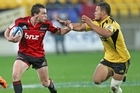 Tom Marshall of the Crusaders is tackled by Alapati Leiua of the Hurricanes. Photo / Getty Images