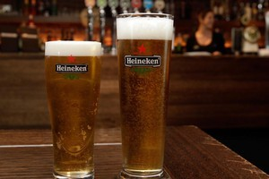 The new Heineken official Rugby World Cup glass (left), which is 20ml smaller than the old glass. Photo / Brett Phibbs