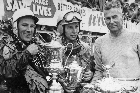 Stirling Moss, (left), John Surtees and Pat Hoare, (right), with their silverware after the rain-soaked Ardmore race. Photo / APN