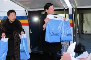 Ballantynes workers Wendy Tauranga (l) and Girl's Day Out host Denise Bird (r) hand out shopping bags at the end of a shopping trip to Timaru for quake hit Christchurch people deprived of their upmarket store. Photo / Amanda Cropp