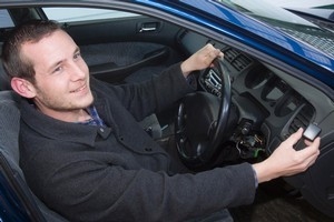 Peter Hurt shows the tiny GPS transmitter fitted to his car which enabled the police to trace the vehicle after it was stolen. Photo / Paul Estcourt