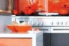 Matching ornaments and accessories tie in with the burnt-orange splashback in the kitchen. Photo / Your Home & Garden