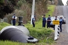 Police search the area close to where a newborn baby was found in a red plastic bag in a stream in Ardmore. Photo / NZPA/Wayne Drought