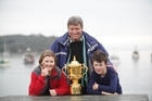 RWC chief executive Martin Snedden shows the cup to Sophie Conner and Marley Wright at  Half Moon Bay School on Stewart Island. Photo / Supplied