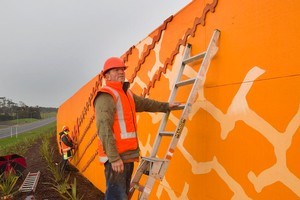 Jeff Thomson fixes his artwork to the noise wall at Brighams Creek Rd on the new Hobsonville Deviation. Photo / Paul Estcourt