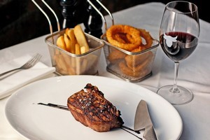 Savannah angus eye fillet on the bone, with sides of steakhouse fries and crumbed onion rings in mini frying baskets. Photo / Sarah Ivey