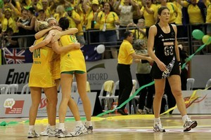 Australian players celebrate victory as Irene van Dyk walks from the court. Photo / Getty Images