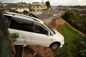 A Mitsubishi Chariot sits precariously over a bank on Eleventh Avenue yesterday.  Photo / Bay of Plenty Times