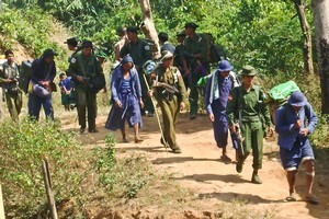 Convict porters (in blue) forced to work for the  Burmese army. Photo / AP