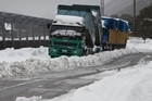 This week's winter storm has caused chaos throughout New Zealand - including trapped trucks in Arthur's Pass - but should start easing soon, although not before one last downpour. Photo / Simon Baker