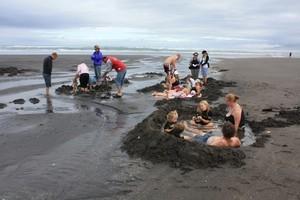 Beach-goers build their own spas at Ocean Beach's Te Puia hot spring. Photo / Supplied