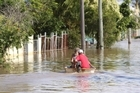 Residents motor down a flooded street in Rockhampton. Photo / Morning Bulletin