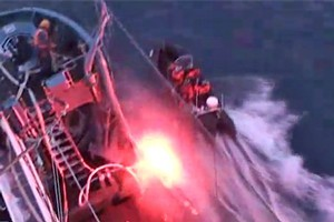 A flash is seen as anti-whaling activists throw a device at the Japanese whaling ship Yushin Maru No. 2.