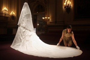 Caroline de Guitaut, curator of the exhibition at Buckingham Palace, adjusts the wedding dress of Catherine, the Duchess of Cambridge. Photo / AFP