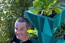 Justin Newcombe with his flourishing herb box. Photo / Richard Robinson