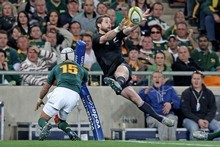 Cory Jane offloads the ball in front of a 94,000-strong crowd in Johannesburg last year, as the All Blacks took their 10th Tri-Nations title. Photo / Getty Images