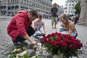 People light candles and lay flowers in central Oslo to pay tribute to the victims of the twin attacks which left over 90 people dead. Photo / AFP