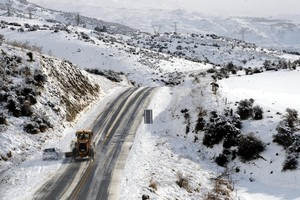 A grader clears snow past an abandonded car on SHW8 between Alexandra and Roxburgh. Photo / Supplied