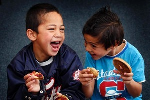 Dawson School students Harlem Phillips (left) and Dominic Kautapa Manuka tuck into their bagels donated by Abe's. Photo / Sarah Ivey