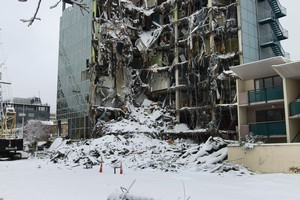 Snow covers the earthquake damaged DTZ House in central Christchurch. Photo / Simon Baker