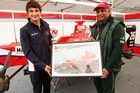 Mitch Evans presents a photo of his car to Tony Fernandes in recognition of the Arden team's first race win. Photo / Supplied