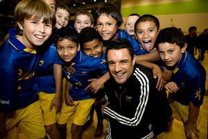 Summerland Primary School pupils surround Dan Carter before their game. Photo / Dean Purcell