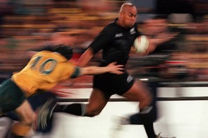 Jonah Lomu evades the tackle of Stephen Larkham during the match between Australia v New Zealand for the Bledisloe Cup. Photo / Allsport