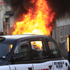 A car, behind the taxi, burns after it was set on fire by rioters in Hackney, east London. Photo / AP