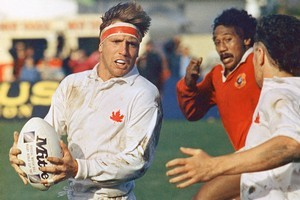 Canada's Stephen Gray prepares to pass to Tom Woods (right) as Tonga's Samiu Mohi applies the pressure at Napier. Canada beat Tonga 37-4. Photo / AP