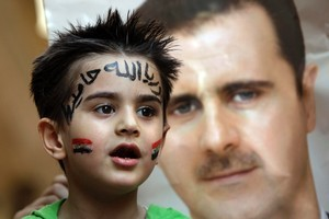 President Bashar al-Assad (background) promises reform while leading  the worst repression in Syria since 1982. Photo / AP
