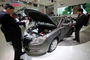 Visitors inspect a new Baojun 630 sedan at the Shanghai International Auto Show. Photo / AP