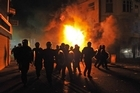 British riot police in front of a burning building in Croydon, South London. Photo / AFP