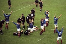 The French players celebrate as the All Blacks reel in shock at the loss.