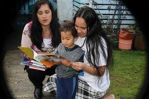 Toni-Lee Hayward (L) from He Waka Matauranga presents books to Kara Hetaraka and her son Kal-El Ngauora, 3. Photo / Greg Bowker