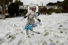 Kate Beentjes skis down her front lawn in the Christchurch suburb of Mt. Pleasant as a polar blast hits New Zealand. Photo / Simon Baker