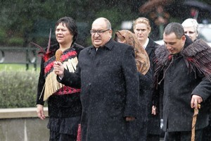 Sir Anand Satyanand holds aloft a mere in heavy rain during yesterday's powhiri. Photo / Mark Mitchell