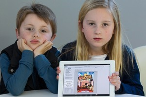 Blake Hammond (7) and sister Zoe (8) with the expensive game they downloaded onto their mother's iPad. Photo / Paul Estcourt