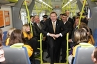 John Key and Nathan Guy chat with children from Kapiti Primary School aboard a new Matangi train. Photo / Mark Mitchell