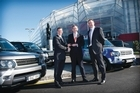 James Yates (centre), Kit McConnell (left) and Land Rover's Ross Young at Eden Park with some of the branded vehicles. Photo / Supplied
