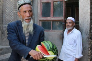 A friendly resident of Kashgar's old quarter offers to share his snack. Photo / Jim Eagles