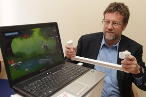 Im-Able's Geoff Todd with a device that helps stroke patients regain muscle control. Photo / Mark Mitchell