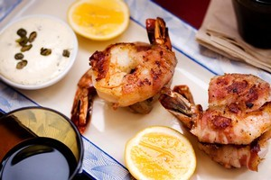 Pancetta-wrapped prawns with caper aioli and lemon. Photo / Babiche Martens