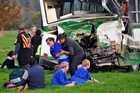 Students sit stunned and bewildered as helpers assist the injured after yesterday's crash near Ruatoki.  Photo / Supplied