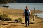 Inspector Steve Bullock scans the lake from an area of shoreline exposed by the lowering of the water level. Photo / Alan Gibson