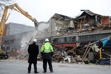 Insurance and demolition workers watch as the earthquake damaged building on the corner of Gloucester and Manchester Streets is demolished in Christchurch. Photo / NZ Herald 