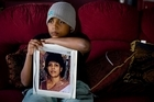 Dylan Raman, 12, holds a photo of his mother, Pushpa,  who died from meningococcal septicaemia after her illness was misdiagnosed. Photo / Dean Purcell